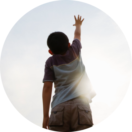 Young child reaching towards the sunny sky